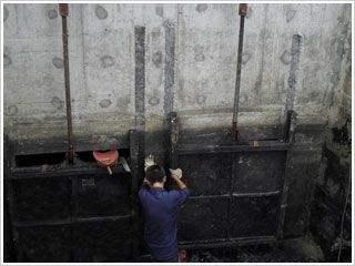 工人对铸铁闸门进行维护